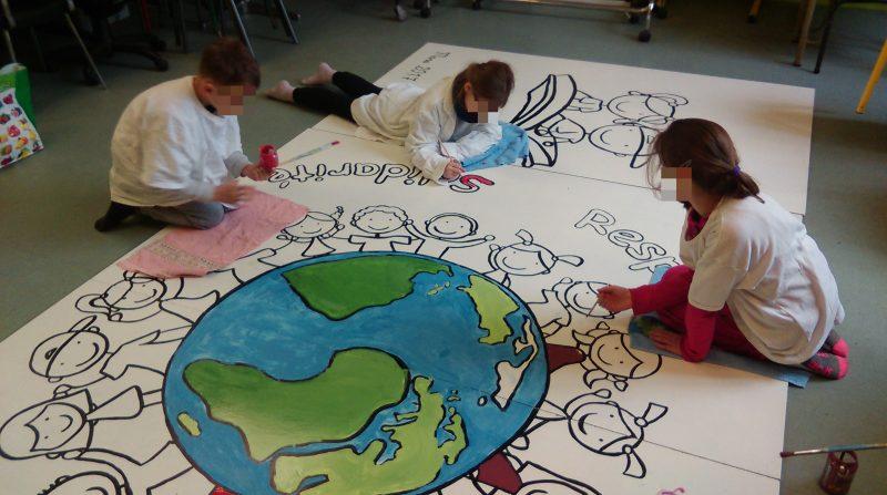 Les élèves peignant la fresque de l'école